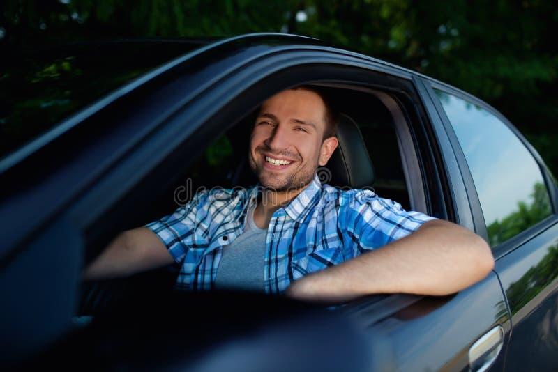 Junger Mann beim Autolächeln lizenzfreies stockbild