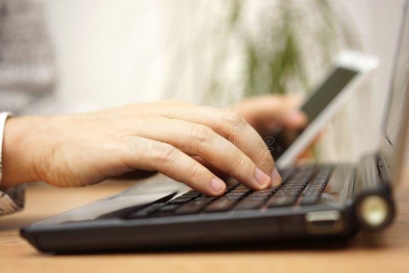 Junger Mann benutzt Laptop-Computer und Handy an den selben stockbilder