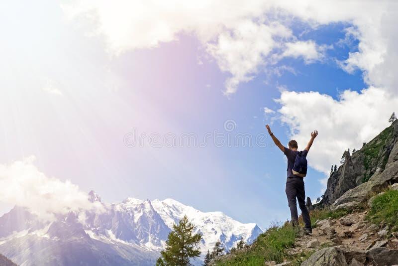 Junger Mann in den Bergen, die mit seinen Händen stehen, hob an lizenzfreies stockfoto