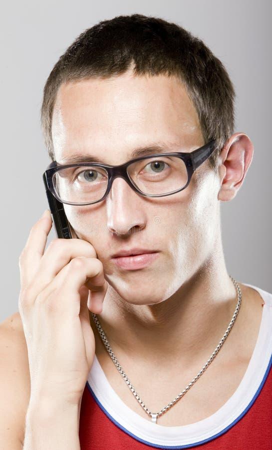 Junger Mann in den Gläsern mit Handy stockfoto