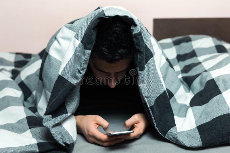 Junger Mann in den Pyjamas unter Verwendung eines Mobiltelefons lizenzfreies stockfoto
