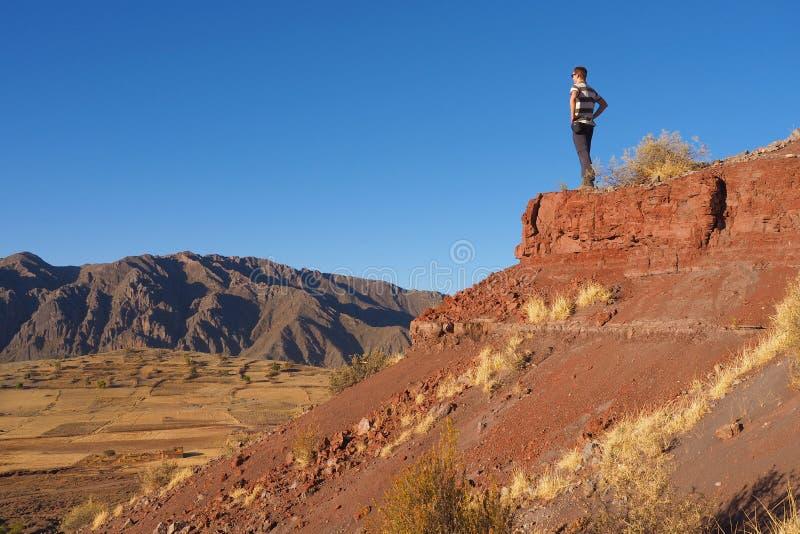 Junger Mann, der über trockene und leere Landschaft in Bolivien aufpasst stockfoto