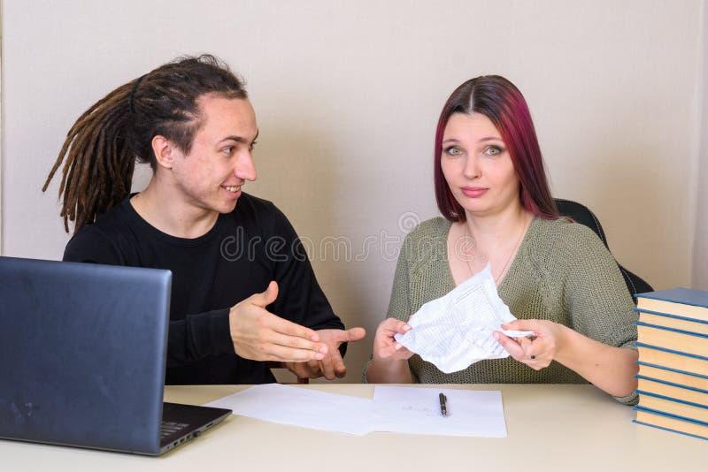 Junger Mann in der Überraschung zeigt ein zerknittertes Papier in den Händen eines Mädchens lizenzfreie stockbilder
