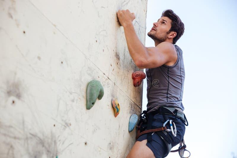 Junger Mann, der Übung im Bergsteigen auf Praxiswand tut stockbilder