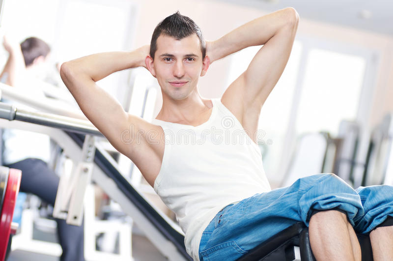 Junger Mann, der Übungen an der Gymnastik tut stockfotografie