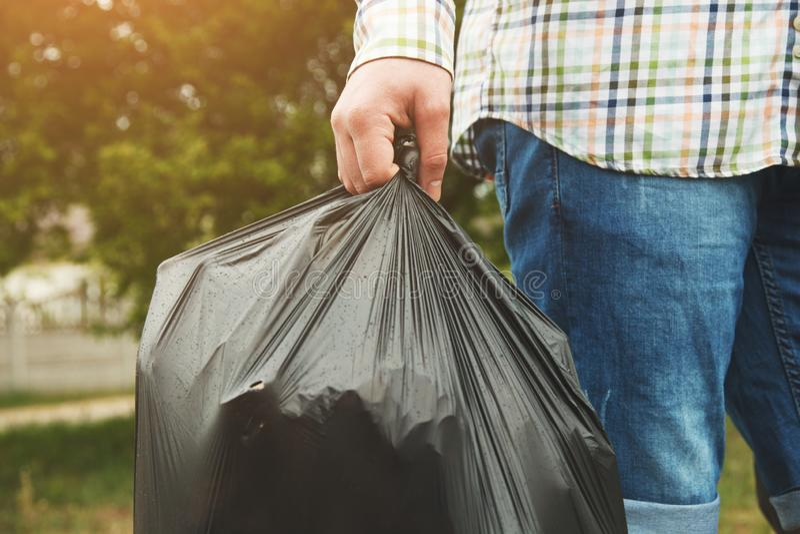 Junger Mann, der Abfall herausnimmt stockfoto