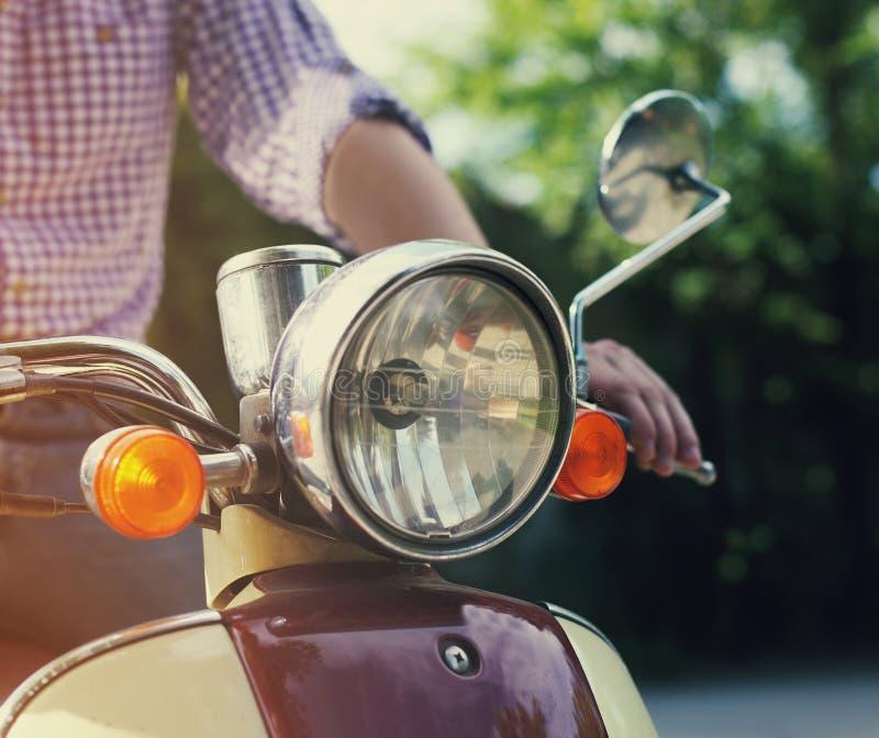 Junger Mann, der alten Retro- Roller reitet lizenzfreie stockfotos