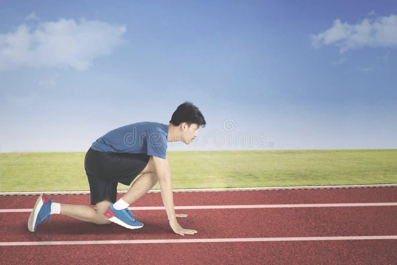 Junger Mann in der Anfangsposition zu laufen lizenzfreie stockbilder