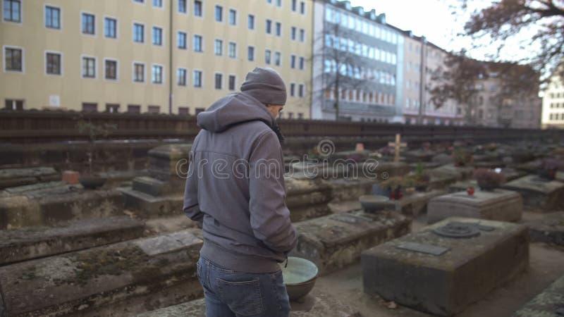 Junger Mann, der auf alten Kirchhof zwischen Gr?ber, historischer Platz, Ged?chtnis geht lizenzfreies stockbild