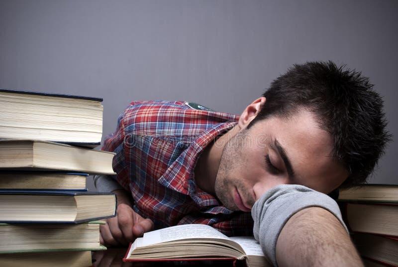 Junger Mann, der auf Büchern schläft stockbilder