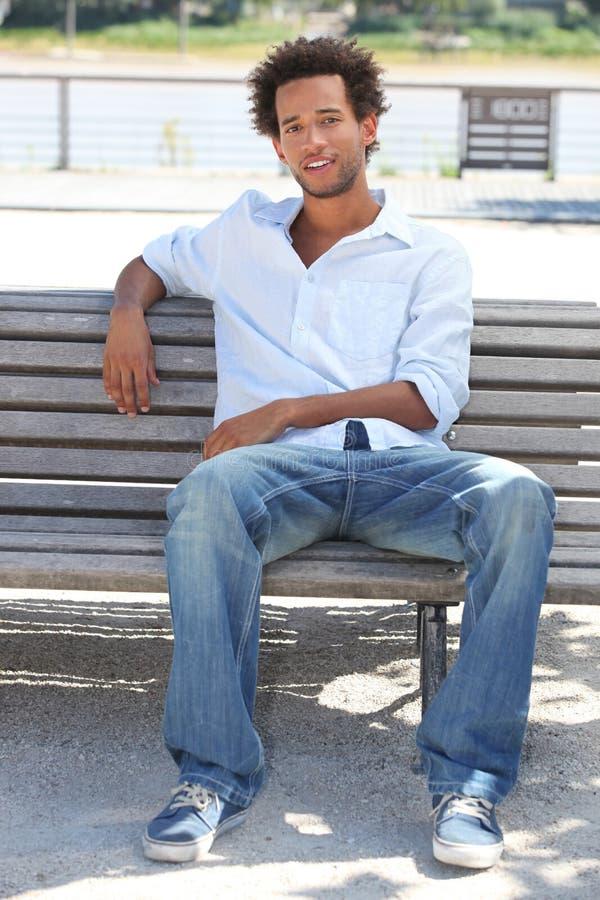 Junger Mann, der auf Bank sitzt lizenzfreie stockbilder