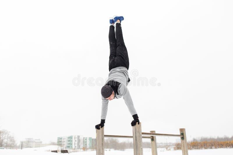 Junger Mann, der auf Barren im Winter trainiert lizenzfreie stockfotografie