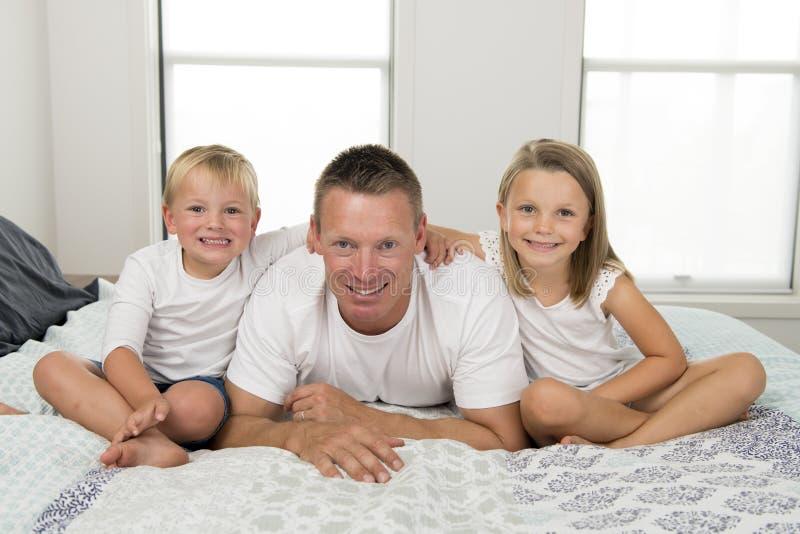 Junger Mann, der auf Bett zusammen mit ihren kleinen altes Sohn- und Tochterspielen des Bonbons 3 und 7 Jahren glücklich in Famil stockfoto