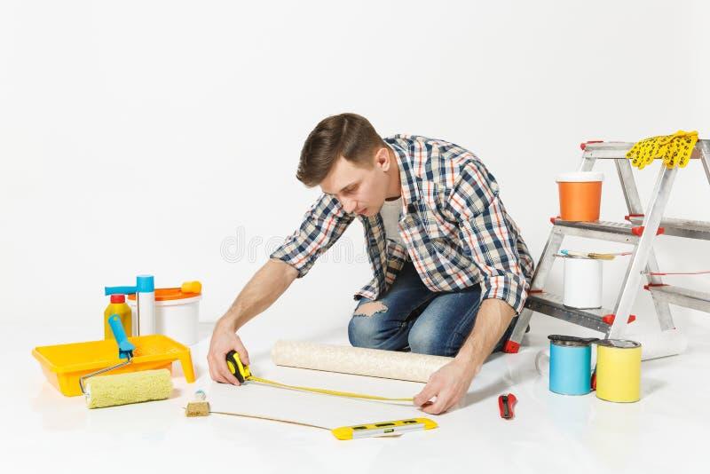 Junger Mann, der auf Boden mit Rolle der Tapete, Maßband, Bleistift, Instrumente für Erneuerungswohnungsraum sitzt stockbilder