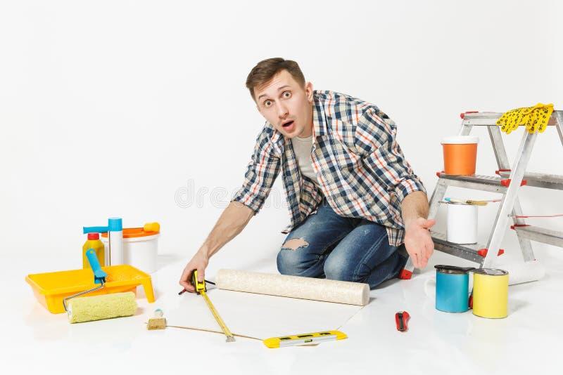 Junger Mann, der auf Boden mit Rolle der Tapete, Maßband, Bleistift, Instrumente für Erneuerungswohnungsraum sitzt lizenzfreie stockfotografie