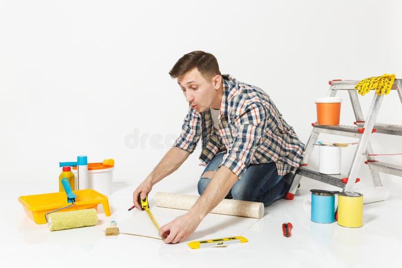 Junger Mann, der auf Boden mit Rolle der Tapete, Maßband, Bleistift, Instrumente für Erneuerungswohnungsraum sitzt lizenzfreie stockbilder