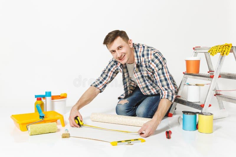 Junger Mann, der auf Boden mit Rolle der Tapete, Maßband, Bleistift, Instrumente für Erneuerungswohnungsraum sitzt lizenzfreies stockfoto