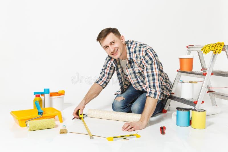 Junger Mann, der auf Boden mit Rolle der Tapete, Maßband, Bleistift, Instrumente für Erneuerungswohnungsraum sitzt lizenzfreie stockfotos