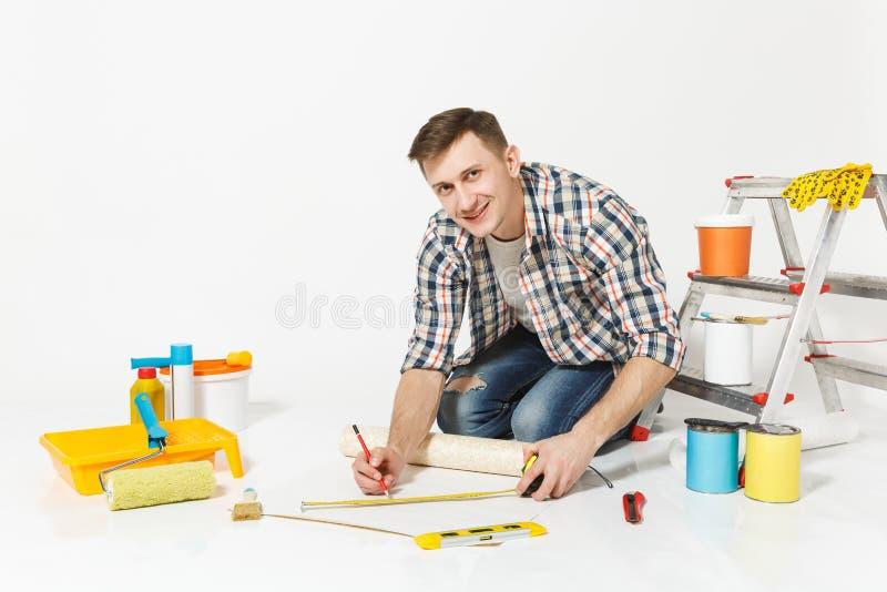 Junger Mann, der auf Boden mit Rolle der Tapete, Maßband, Bleistift, Instrumente für Erneuerungswohnungsraum sitzt lizenzfreies stockbild