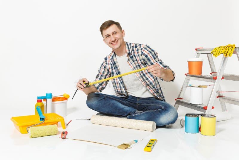 Junger Mann, der auf Boden mit Rolle der Tapete, Maßband, Bleistift, Instrumente für Erneuerungswohnungsraum sitzt stockfotos