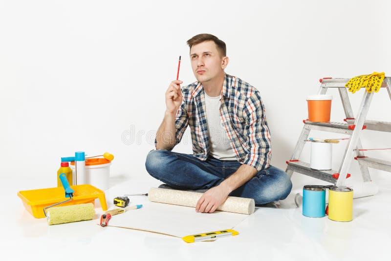 Junger Mann, der auf Boden mit Tapetenrolle, Bleistift, Instrumente für den Erneuerungswohnungsraum lokalisiert auf Weiß sitzt lizenzfreie stockfotografie
