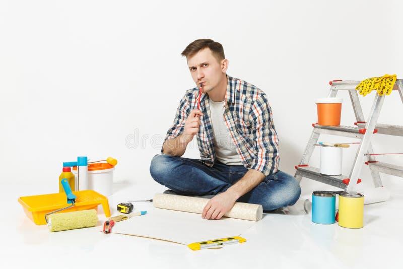 Junger Mann, der auf Boden mit Tapetenrolle, Bleistift, Instrumente für den Erneuerungswohnungsraum lokalisiert auf Weiß sitzt stockfotos