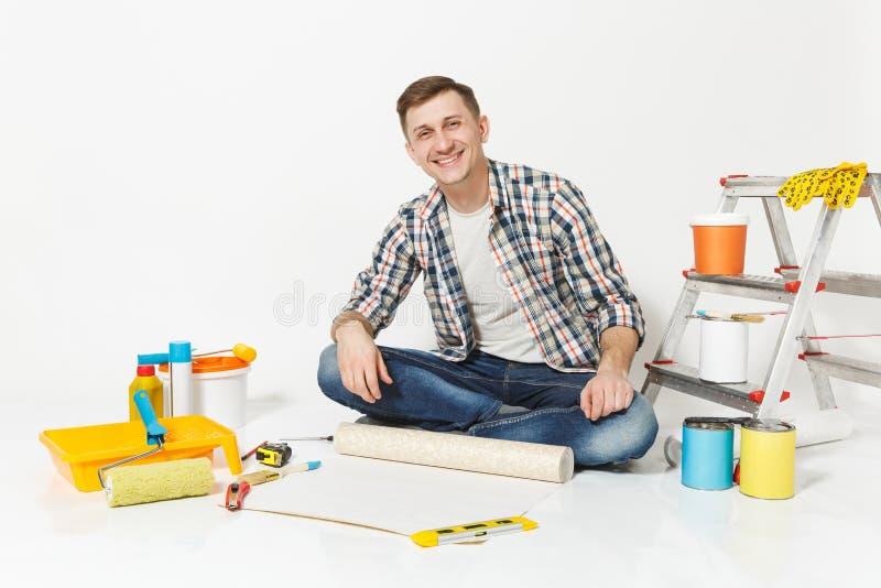 Junger Mann, der auf Boden mit Tapetenrolle, Bleistift, Instrumente für den Erneuerungswohnungsraum lokalisiert auf Weiß sitzt lizenzfreie stockfotos