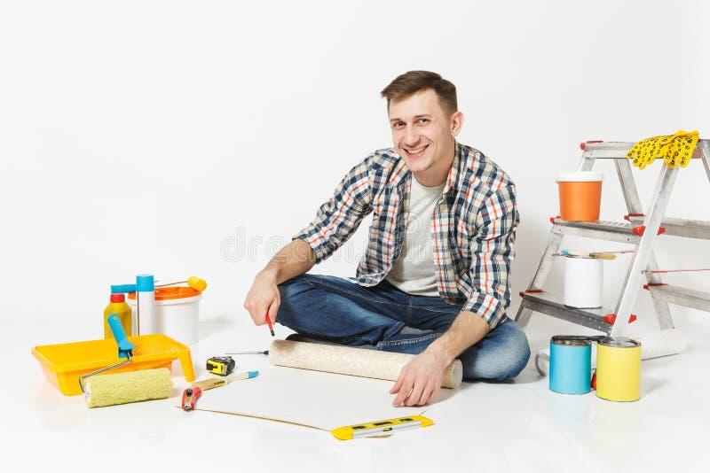Junger Mann, der auf Boden mit Tapetenrolle, Bleistift, Instrumente für den Erneuerungswohnungsraum lokalisiert auf Weiß sitzt stockbilder