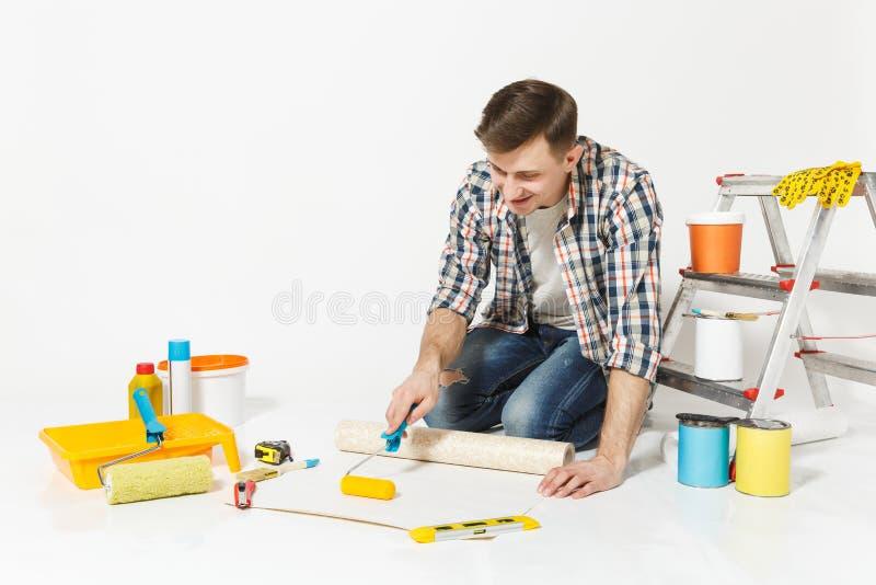 Junger Mann, der auf Boden mit Tapetenrolle, Farbenrolle, Instrumente für den Erneuerungswohnungsraum an lokalisiert sitzt stockfoto