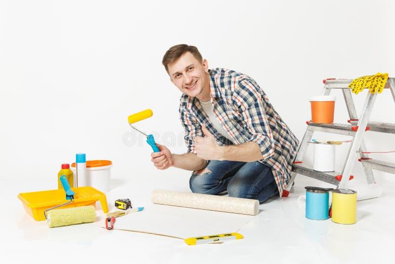 Junger Mann, der auf Boden mit Tapetenrolle, Farbenrolle, Instrumente für den Erneuerungswohnungsraum an lokalisiert sitzt stockfotos