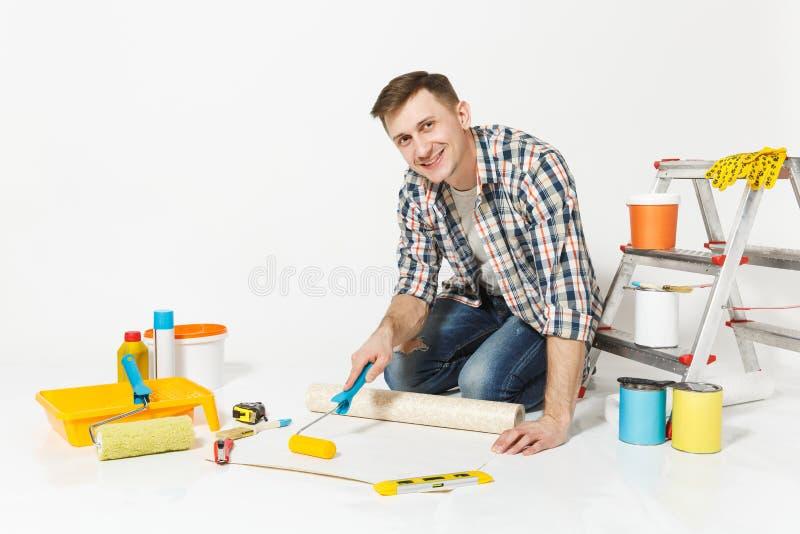 Junger Mann, der auf Boden mit Tapetenrolle, Farbenrolle, Instrumente für den Erneuerungswohnungsraum an lokalisiert sitzt stockbild