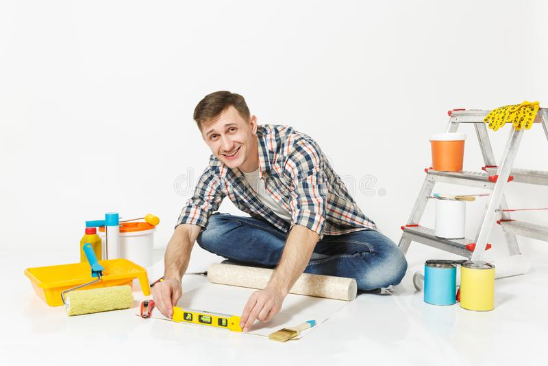 Junger Mann, der auf Boden mit Tapetenrolle, Gebäudeblasen-Geistniveau, Instrumente für Erneuerungswohnung sitzt lizenzfreie stockfotografie