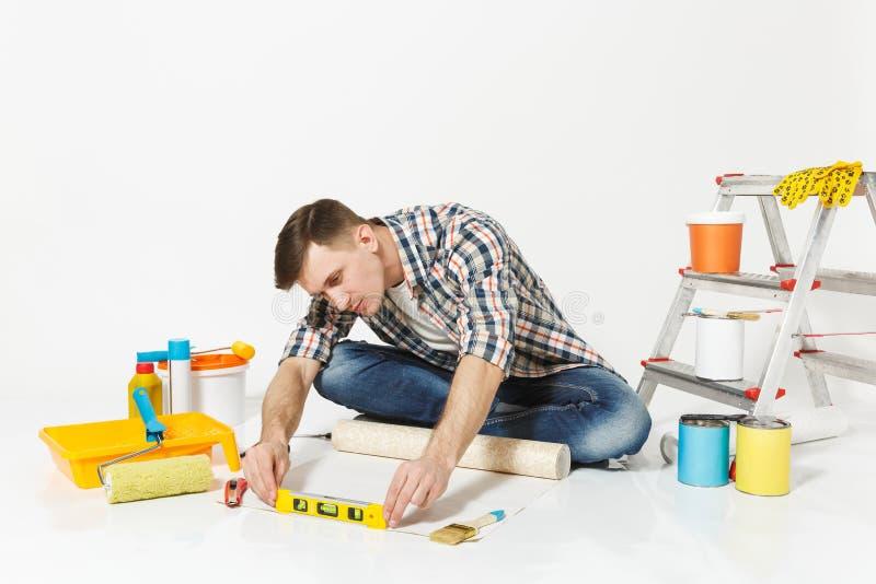 Junger Mann, der auf Boden mit Tapetenrolle, Gebäudeblasen-Geistniveau, Instrumente für Erneuerungswohnung sitzt stockbilder