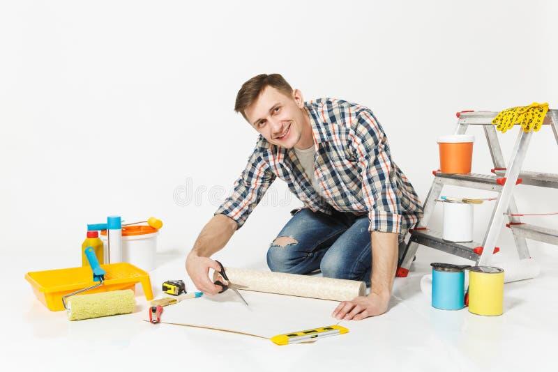 Junger Mann, der auf Boden mit Tapetenrolle, Scheren, Instrumente für den Erneuerungswohnungsraum lokalisiert auf Weiß sitzt lizenzfreie stockfotos