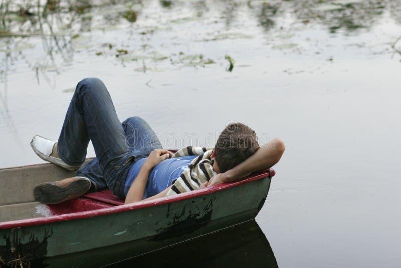 Junger Mann, der auf Boot schläft lizenzfreie stockbilder
