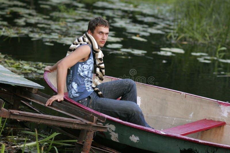 Junger Mann, der auf Boot sitzt stockfotografie