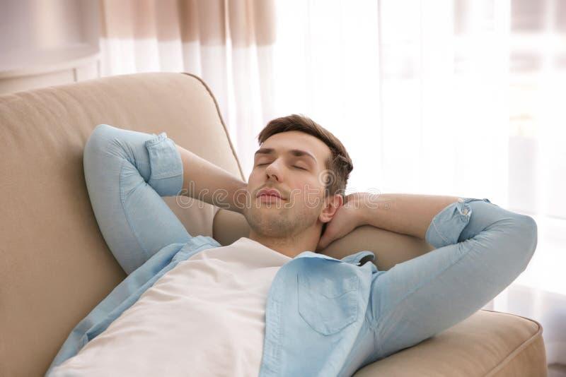 Junger Mann, der auf Couch mit den Händen hinter seinem Kopf stillsteht lizenzfreie stockfotos