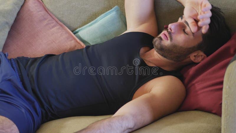 Junger Mann, der auf der Couch stillsteht stockfotografie