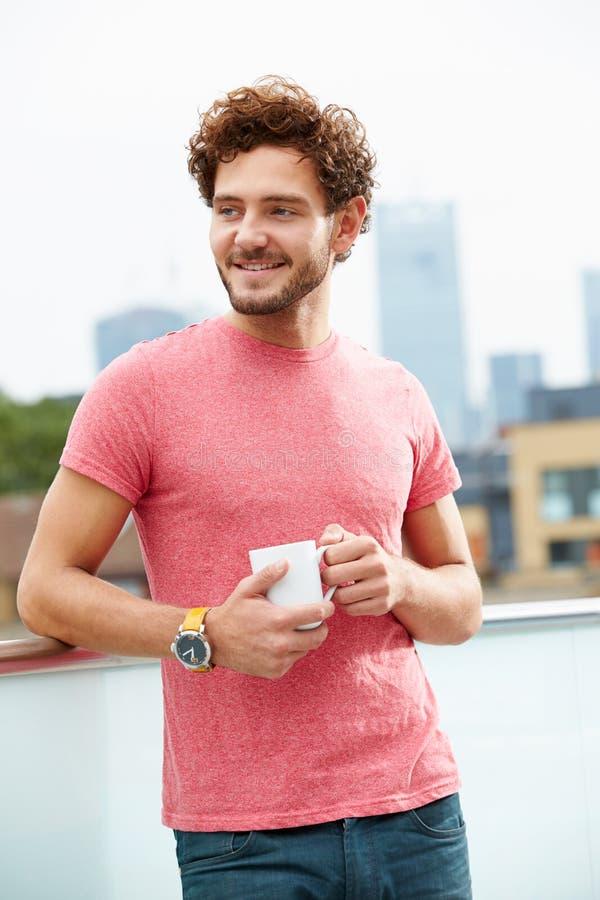 Junger Mann, der auf Dach-Terrasse mit Tasse Kaffee sich entspannt stockfotografie