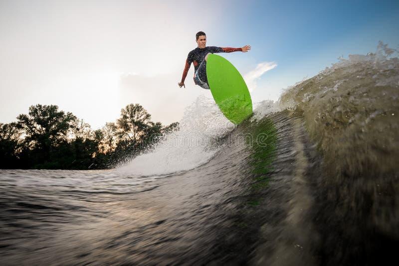 Junger Mann, der auf das wakeboard auf dem See springt lizenzfreie stockbilder