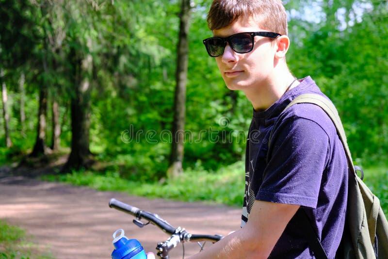 Junger Mann, der auf dem Berg nahe dem Fahrrad sitzt Er untersucht tr?umerisch den Abstand Tr?gt Lebensstil zur Schau lizenzfreie stockbilder