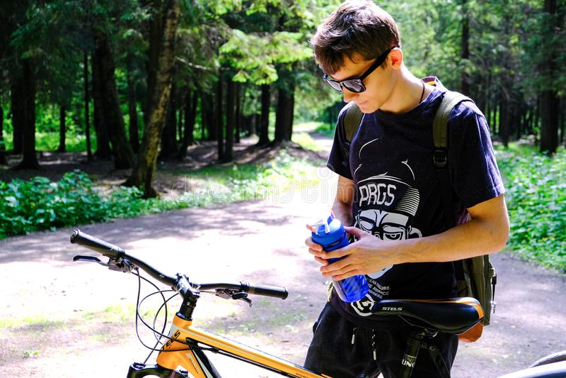 Junger Mann, der auf dem Berg nahe dem Fahrrad sitzt Er untersucht tr?umerisch den Abstand Tr?gt Lebensstil zur Schau St Petersbu stockfotos