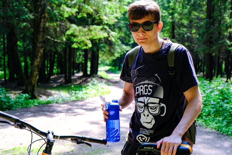 Junger Mann, der auf dem Berg nahe dem Fahrrad sitzt Er untersucht tr?umerisch den Abstand Tr?gt Lebensstil zur Schau St Petersbu lizenzfreie stockfotos