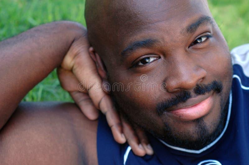 Junger Mann, der auf dem Rasen sich entspannt stockfotos