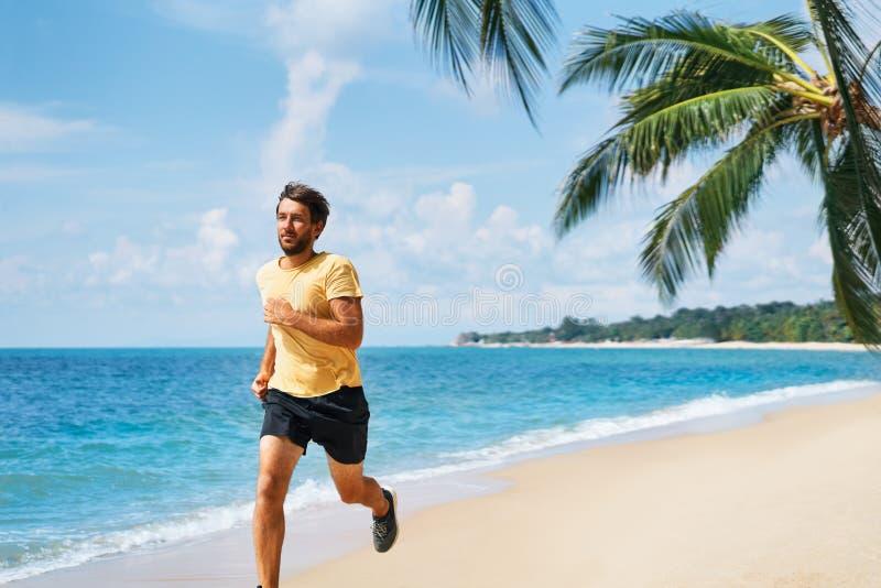 Junger Mann, der auf dem Seeufer des tropischen Strandes läuft stockfotografie