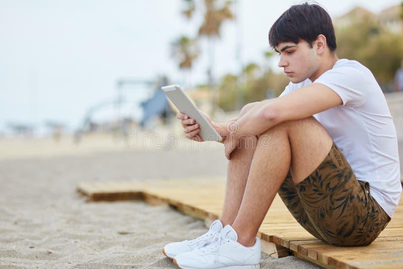 Junger Mann, der auf dem Strand hält Tablette sitzt stockbild