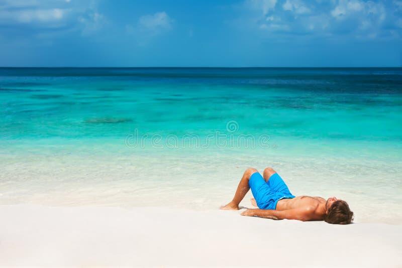 Junger Mann, der auf dem Strand sich entspannt stockbilder