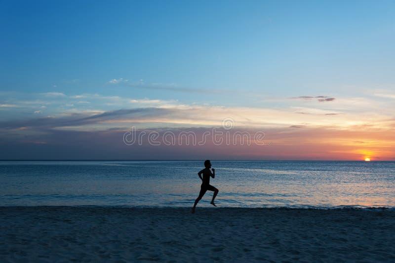 Junger Mann, der auf den Strand läuft stockbild