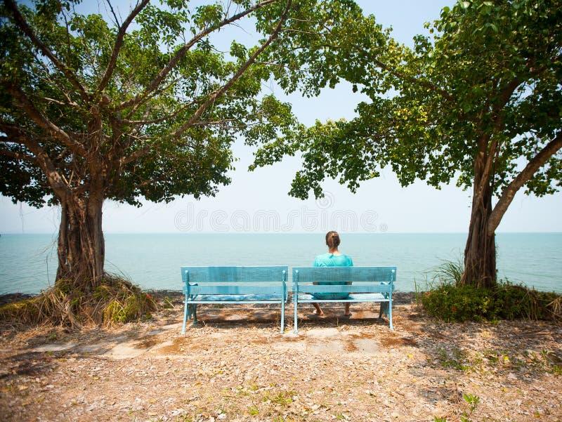 Junger Mann, der auf der Bank gegenüberstellt das Meer sitzt stockfotos