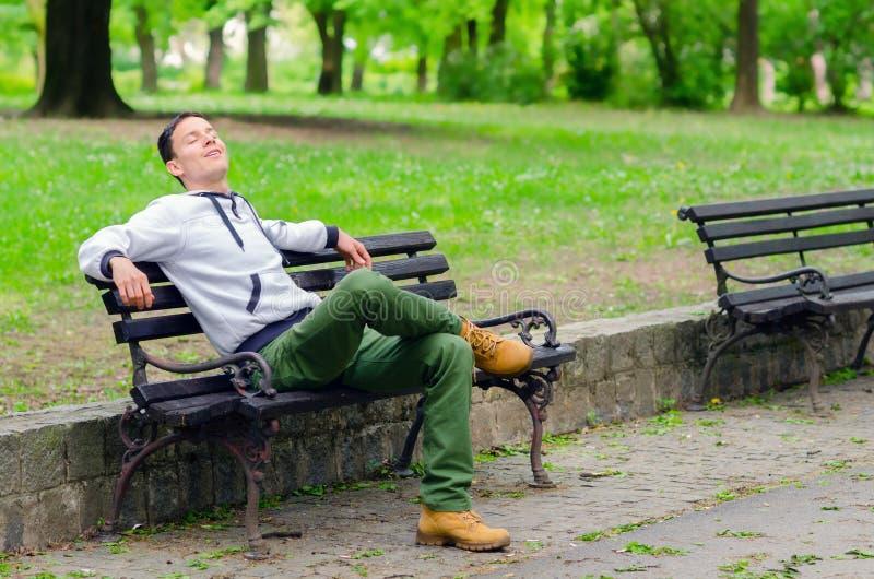 Junger Mann, der auf der Bank im Park träumt stockfotografie